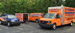 Water Damage Restoration Trucks And Van Outside Job Site